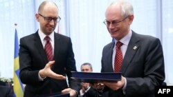 European Council President Herman Van Rompuy (right) exchanges documents with Ukrainian Prime Minister Arseniy Yatsenyuk during the signing of the political provisions of the bloc's Association Agreement with Ukraine in Brussels on March 21.