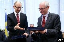 Український прем'єр Арсеній Яценюк і президент Європейської ради Герман Ван Ромпей під час підписання політичної частини угоди з ЄС, 21 березня 2014 року