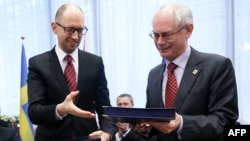 Բելգիա -- Եվրոպական խորհրդի նախագահ Հերման Վան Ռոմպեյը (աջ) և Ուկրաինայի վարչապետ Արսենի Յացենյուկը փոխանակում են ստորագրված փաստաթուղթը, 21 մարտի, 2014