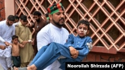 A volunteer carries an injured boy to a hospital, following multiple bomb blasts in Jalalabad on August 19.