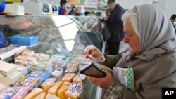A woman counts her money as she buys a piece of cheese at a city market in Minsk in May.