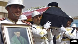 An honor guard carries the coffin of Abdul Aziz al-Hakim upon its arrival at Baghdad International Airport.