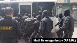 Сотрудники специального отряда полиции быстрого реагирования заталкивают задержанного в автобус. Астана, 23 июня 2018 года.