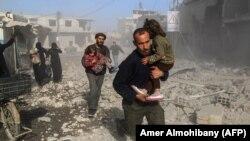 Сирийцы среди развалин домов вблизи Дамаска