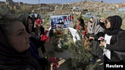FILE: Afghan women rights activists protest on the grave of 27-year-old woman, Farkhunda, who lynched by a mob in Kabul in Kabul in March 2015.