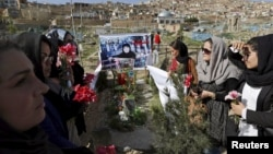 Members of an Afghan women's rights group hold flowers as they gather at the grave of Farkhunda, who was beaten with sticks and set on fire by a crowd of men in Kabul.