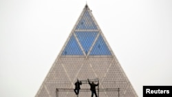Двое рабочих на фоне Дворца мира и согласия. Астана.