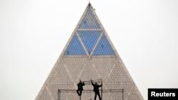 Рабочие на фоне Дворца мира и согласия (известного также как Пирамида) в Астане. Архивное фото.