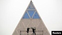 Астанадағы Бейбітшілік және келісім сарайы (Пирамида деп те атайды) маңында жұмыс істеп жатқан адамдар. (Көрнекі сурет.)