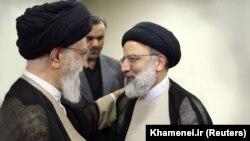 Иранның рухани көсемі аятолла Хаменеи (сол жақта) және жоғары сот төрағасы, президенттіктен үміткер Эбрахим Раиси.