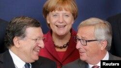 Еурокомиссияның қызметінен кетіп бара жатқан президенті Жозе Мануэль Баррозу (сол жақта) мен жаңа сайланған басшысы Жан-Клод Юнкер (оң жақта) және Германия канцлері Ангела Меркель. Брюссель, 23 қазан 2014 жыл.