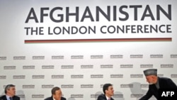 Afghan President Hamid Karzai (standing) shakes hands with British Foreign Minister David Miliband after making a speech at the opening session of the Afghanistan Conference in London on January 28.