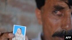 Мужчина держит фотграфию Фарзаны Парвин, которую родственники забили камнями. 30 мая 2014 года.