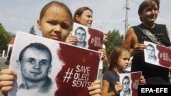 Protesters outside the Russian Embassy in Kyiv hold banners calling for Moscow to release Oleh Sentsov.