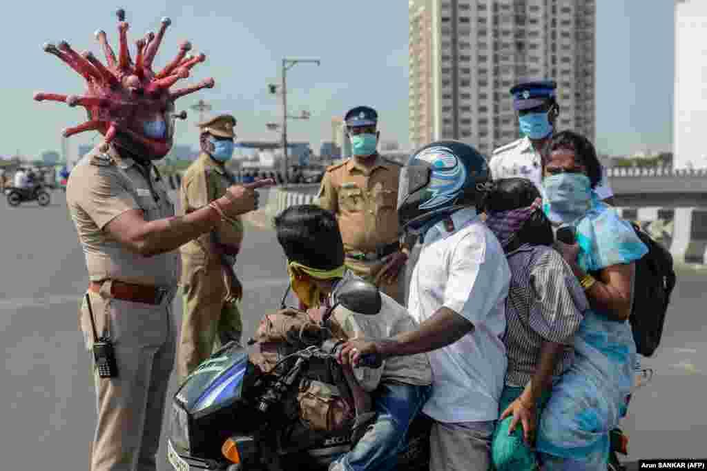 Еще один полицейский в коронавирусном шлеме. Раджеш Бабу доходчиво объясняет семье на мотоцикле, что означает карантин в Индии.