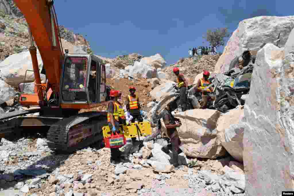 Rescue workers stand beside the wreckage of a damaged truck after the fatal incident in the marble quarry.