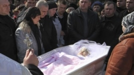 People pay their respects at the coffin of Oksana Makar during her funeral outside the town of Mykolayiv on March 31.
