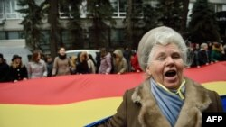 Женщина на фоне молдавского флага во время акции протеста в Кишиневе.