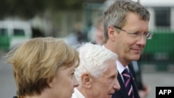 German Chancellor Angela Merkel (left) and German President Christian Wulff (far right) welcome Pope Benedict upon his arrival in Berlin.