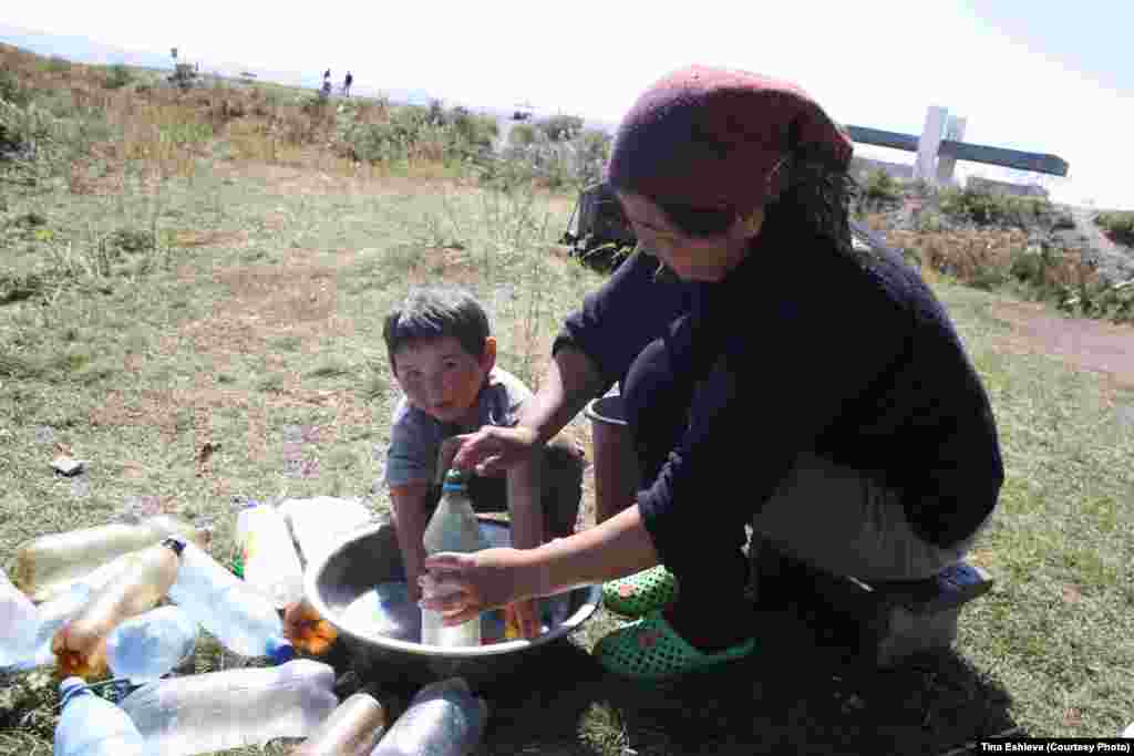 Cуусамыр - Малыш помогает маме мыть пластиковые бутылки. В которые потом будет разлит кумыс, чтобы можно было его продавать проезжающим мимо туристам и дальнобойщикам. Фото Тины Эшиевой