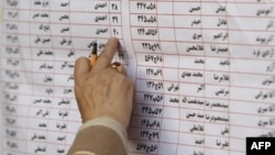 An Iranian voter chooses candidates from a list hanging on a bus designated as a polling station in Tehran during the March 2008 national elections.