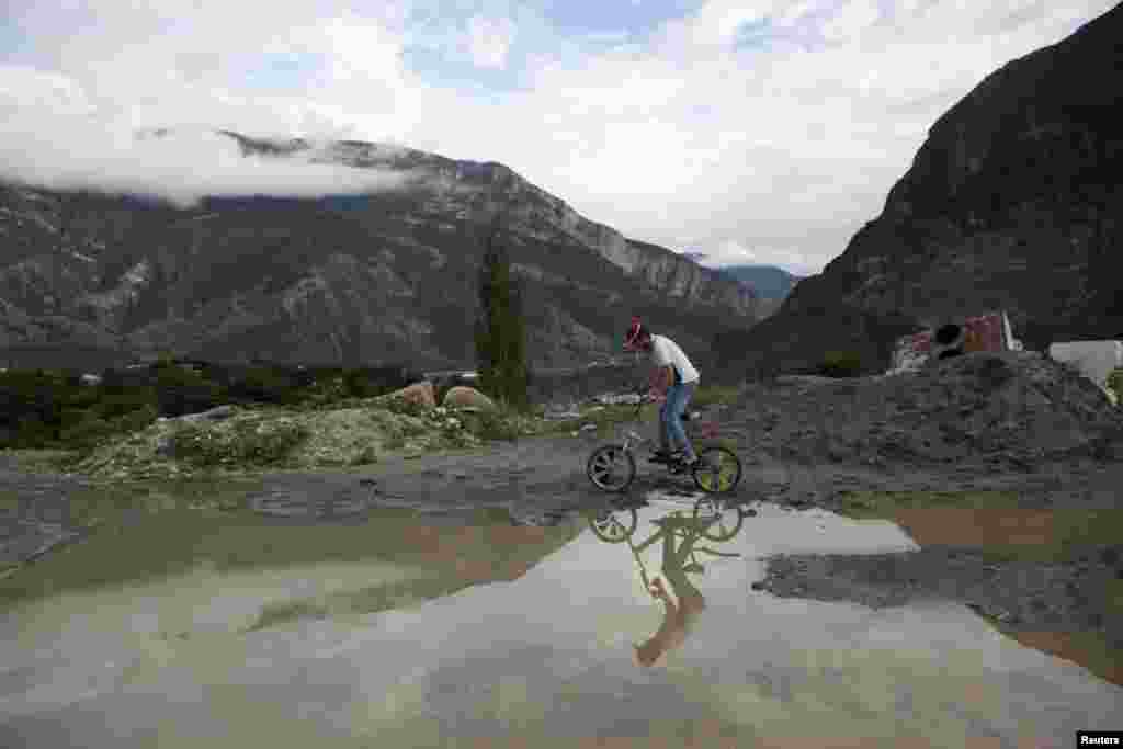 A man rides his bicycle in the mountain village of Gimry.