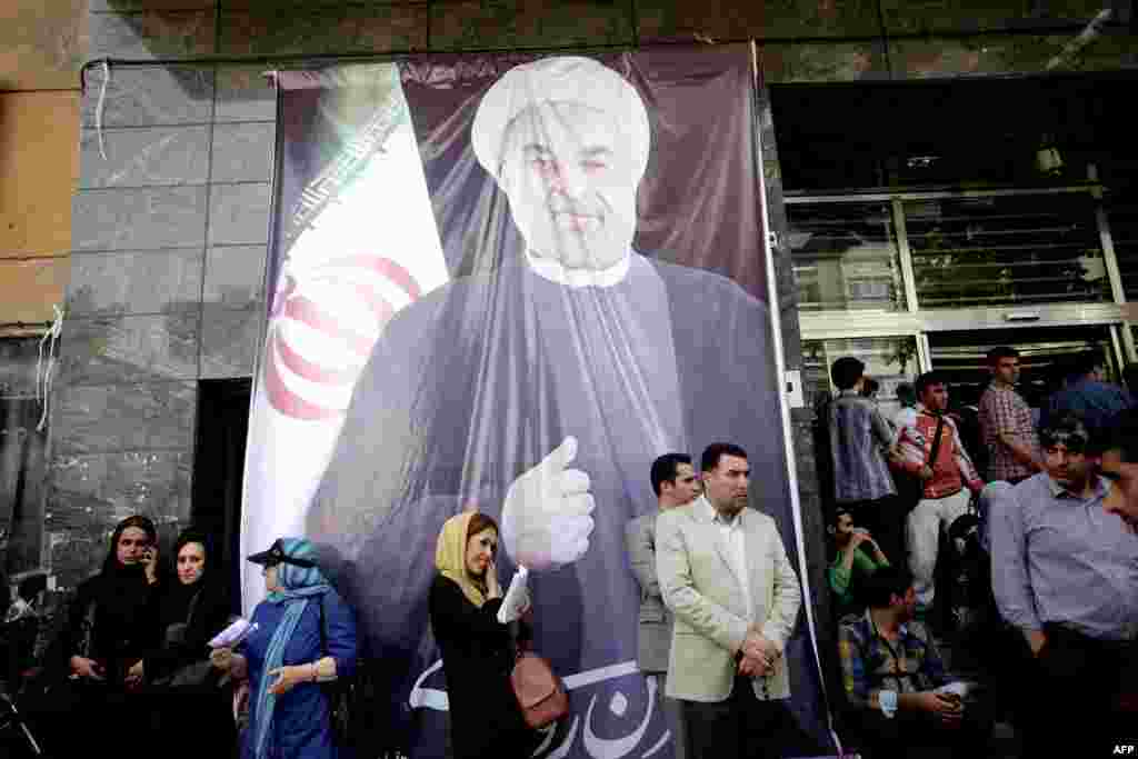 People gather under a portrait of Rohani outside his campaign headquarters after the announcement of his victory on June 15.