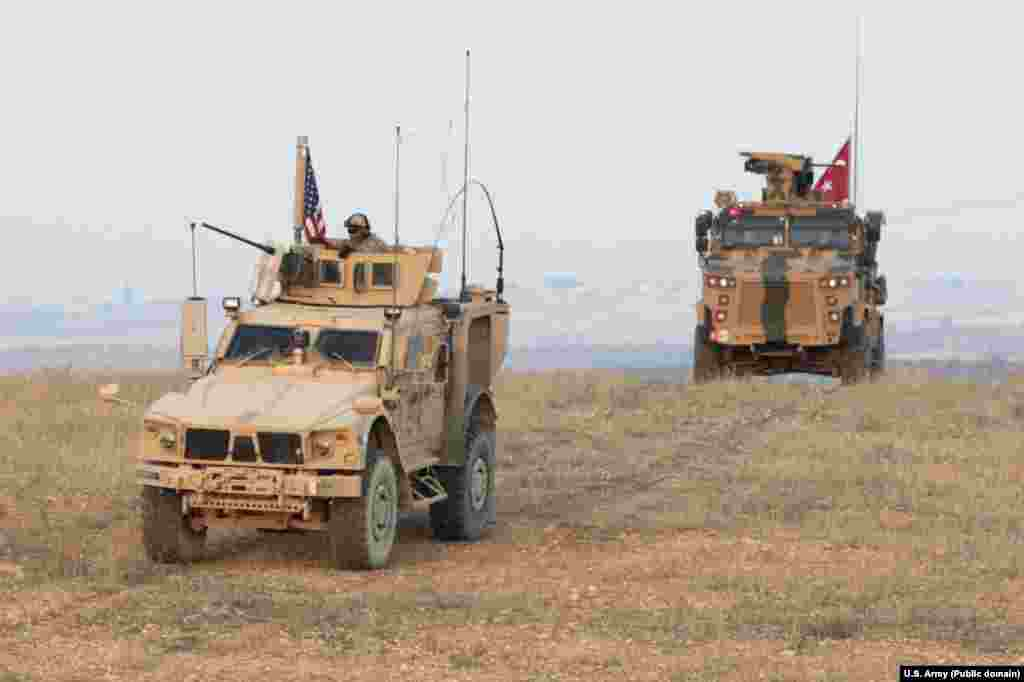 "U.S. and Turkish forces conduct joint patrols on the outskirts of Manbij in November 2018. Syria is today an ""ever congested"" battle space, with U.S.-, Turkish-, Syrian-, Russian-, and Iranian-affiliated fighters all variously cooperating and clashing in the country."