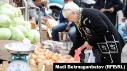 Женщина выбирает овощи на рынке. Алматы, 16 октября 2012 года.