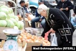 Женщина покупает овощи на рынке в Алматы.