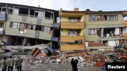 Turkey -- Earthquake survivors stand in front of a damaged building in Ercis, 26Oct2011