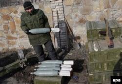 """Боец """"армии Новороссии"""" держит в руках артиллерийский снаряд, окрестности Дебальцева, февраль 2015-го года"""