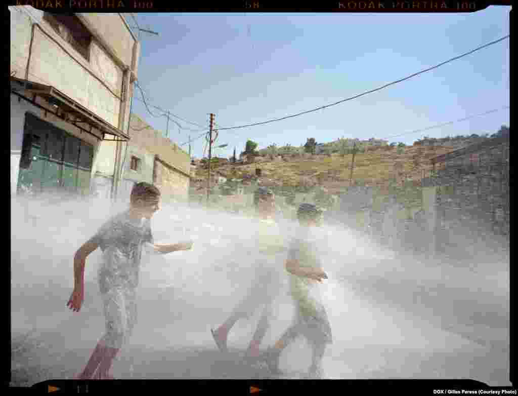 "Gilles Peress, Al Bustan, a Neighborhood in the Village of Silwan, East Jerusalem, 2011   Gilles Peress makes an astute observation of the psychological ""temperature"" of Israel and the West Bank. His photographs, taken on the streets, represent their inhabitants as embodiments of the extremities of perspectives that shape Israel."