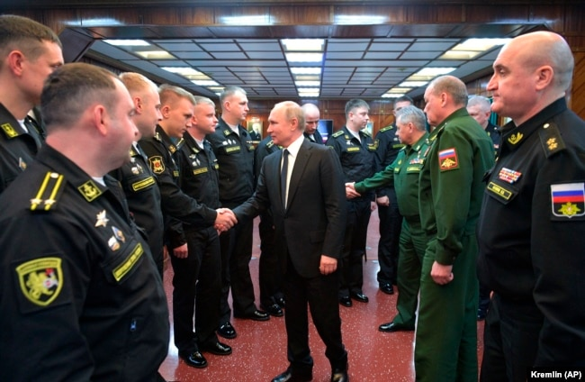 Vladimir Putin shakes hands with officers while visiting the a missile cruiser in the Black Sea.