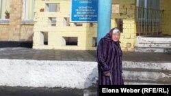Пожилая женщина у административного здания в день парламентских выборов. Темиртау, 20 марта 2016 года.