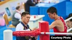 Абылайхан Жусупов (в красной форме) и тренер национальной сборной Казахстана по боксу Мырзагали Айтжанов (слева) во время соревнований в Китае. 29 марта 2016 года. Фото взято с официального веб-сайта Федерации бокса Казахстана.