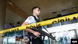 An armed Turkish policeman patrols behind a police line following the attack at Ataturk international airport in Istanbul on June 29.