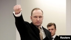 Norwegian mass killer Anders Behring Breivik give a clenched-fist salute as he arrives in court for the second day of his terrorism and murder trial in Oslo on April 17.