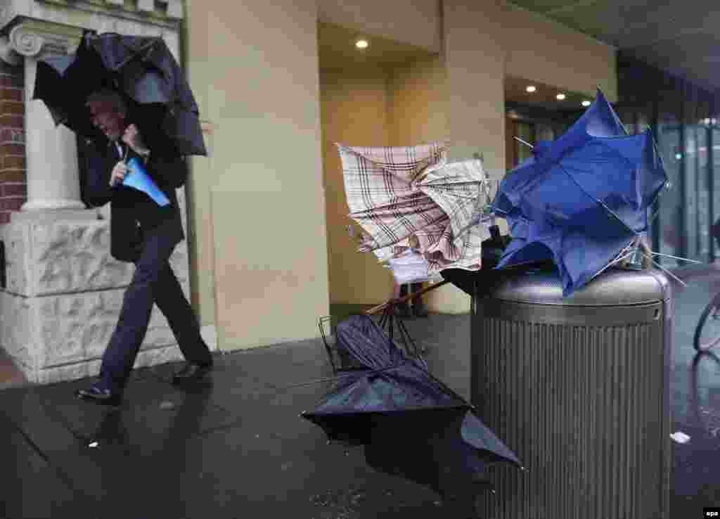 A man passes by discarded umbrellas during heavy rain in New South Wales, Australia. More than 20 people have been rescued from floodwaters and 215,000 homes and businesses are without power as storms lashed New South Wales. (epa/David Moir)