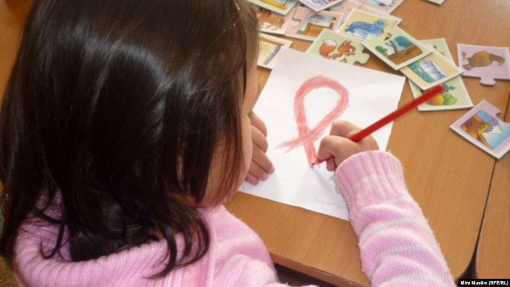 An HIV-infected child draws a Red Ribbon, the international symbol of HIV and AIDS awareness, at the Center for Maternity and Childhood in Shymkent in this 2010 photo.