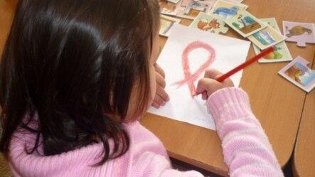 ВИЧ-инфицированная девочка рисует символ борьбы со СПИДом