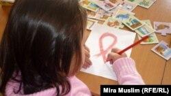 Девочка, оказавшаяся зараженной ВИЧ, рисует символ борьбы со СПИДом. Шымкент, 30 ноября 2010 года.