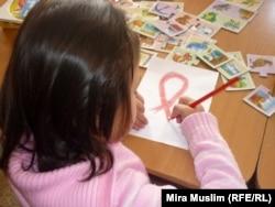 Девочка с диагнозом «ВИЧ-инфекция» рисует символ борьбы со СПИДом. Шымкент, 30 ноября 2010 года.