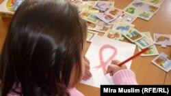 Девочка рисует символ борьбы со СПИДом. Иллюстративное фото.
