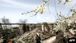 A woman walks past buildings ruined in the August 2008 fighting in South Ossetia's Tskhinvali.
