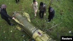 Сирийские повстанцы в провинции Дераа разглядывают обломок ракеты