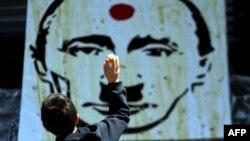 Мальчик бросает яйцо в портрет президента России Владимира Путина, изображенного в виде нацистского диктатора Германии Адольфа Гитлера, во время флешмоба в центре Киева. 24 мая 2014 года.