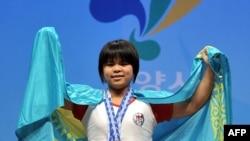 Зульфия Чиншанло, чемпионка мира по тяжелой атлетике, позирует для журналистов после победы. Гоянг, 22 ноября 2009 года.
