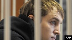 Opposition leader Zmitser Dashkevich sits inside a guarded cage during a court hearing in Minsk on March 22.