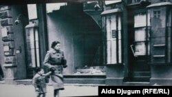 Detalj sa izložbe: Majka i dijete prolaze pored uništene prodavnice